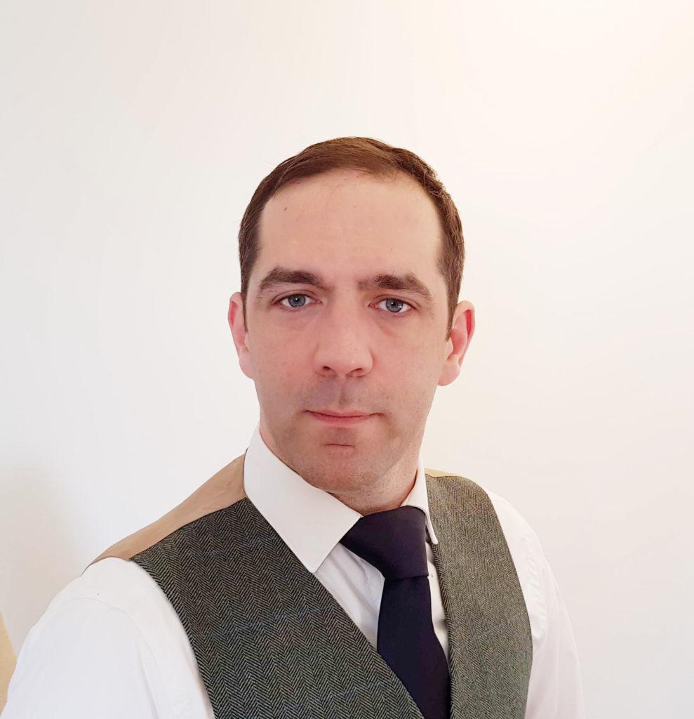 Robin Scott (male human wearing waistcoat, shirt and tie)